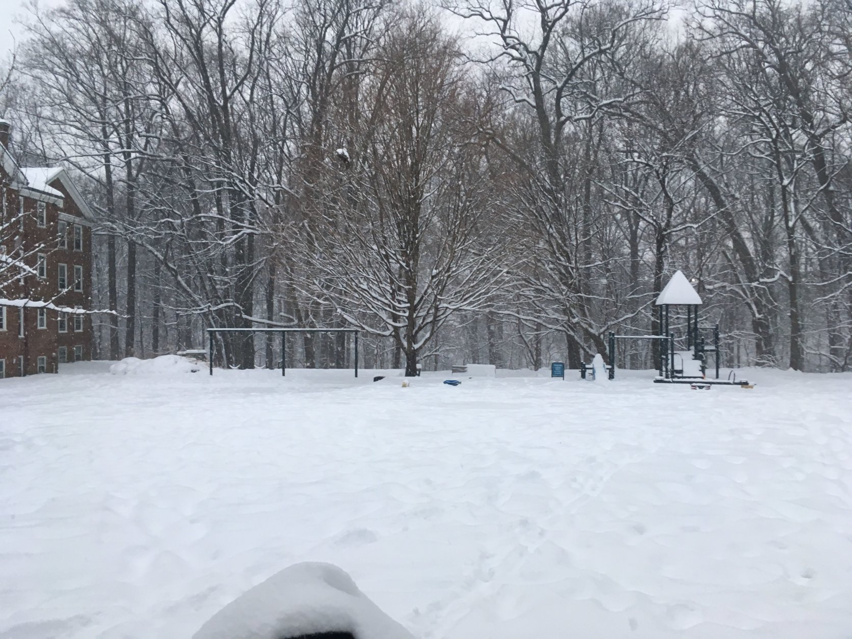 Snow falls amid a playground in McLean Gardens in D.C. (WTOP/Rick Massimo)