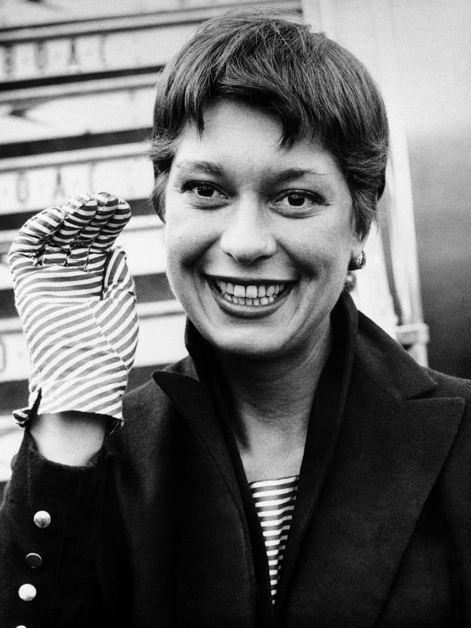 American singing star Carol Channing wears red and white striped gloves with her navy blue coat on arrival at London Airport, May 16, 1955. She will be on holiday here for two weeks, and then goes on to Paris and Istanbul. (AP Photo)