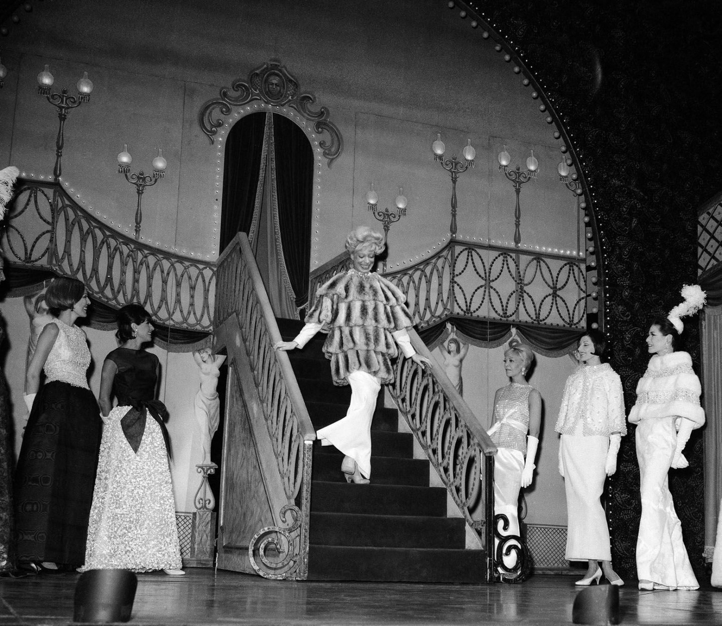 Carol Channing, star of the musical ?Hello, Dolly!? wears a Luis Estevez fur as she descends a stairway during a scene from the show staged as part of a fashion presentation at the St. James Theater in New York, Wednesday, June 3, 1964. (AP Photo)