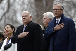 Maryland Gov. Larry Hogan, center, stands between first lady Yumi Hogan, left, and former Florida Gov. Jeb Bush during a rendition of the national anthem at Hogan's inauguration ceremony, Wednesday, Jan. 16, 2019, in Annapolis, Md. Hogan is the first Republican governor to be re-elected in the state since the 1950s. (AP Photo/Patrick Semansky)
