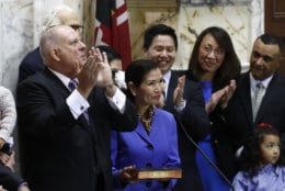 Maryland Gov. Larry Hogan, left, accompanied by his wife Yumi and family, applauds after taking the oath of office inside the State Senate chamber, Wednesday, Jan. 16, 2019, in Annapolis, Md. (AP Photo/Patrick Semansky, Pool)