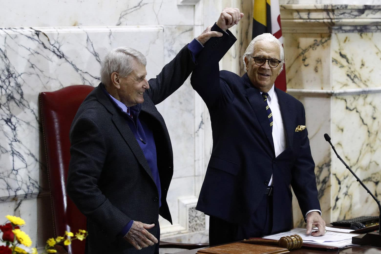 Maryland House Speaker Michael Busch, left, raises Senate President Thomas V. Mike Miller's arm before swearing-in ceremonies for Gov. Larry Hogan and Maryland Lt. Gov. Boyd Rutherford in the State Senate chamber, Wednesday, Jan. 16, 2019, in Annapolis, Md. (AP Photo/Patrick Semansky)