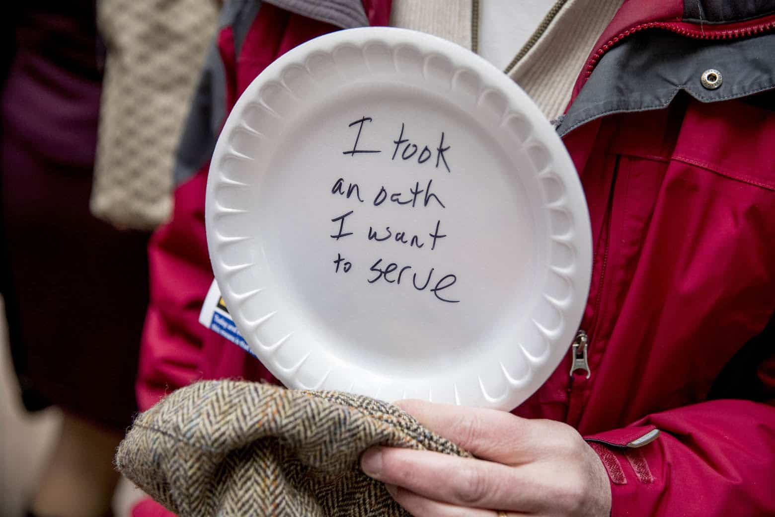 """A furloughed government worker affected by the shutdown holds a sign that reads """"I took an oath I want to serve"""" during a silent protest against the ongoing partial government shutdown on Capitol Hill in Washington, Wednesday, Jan. 23, 2019. Protesters held up disposable plates instead of posters to avoid being arrested. (AP Photo/Andrew Harnik)"""