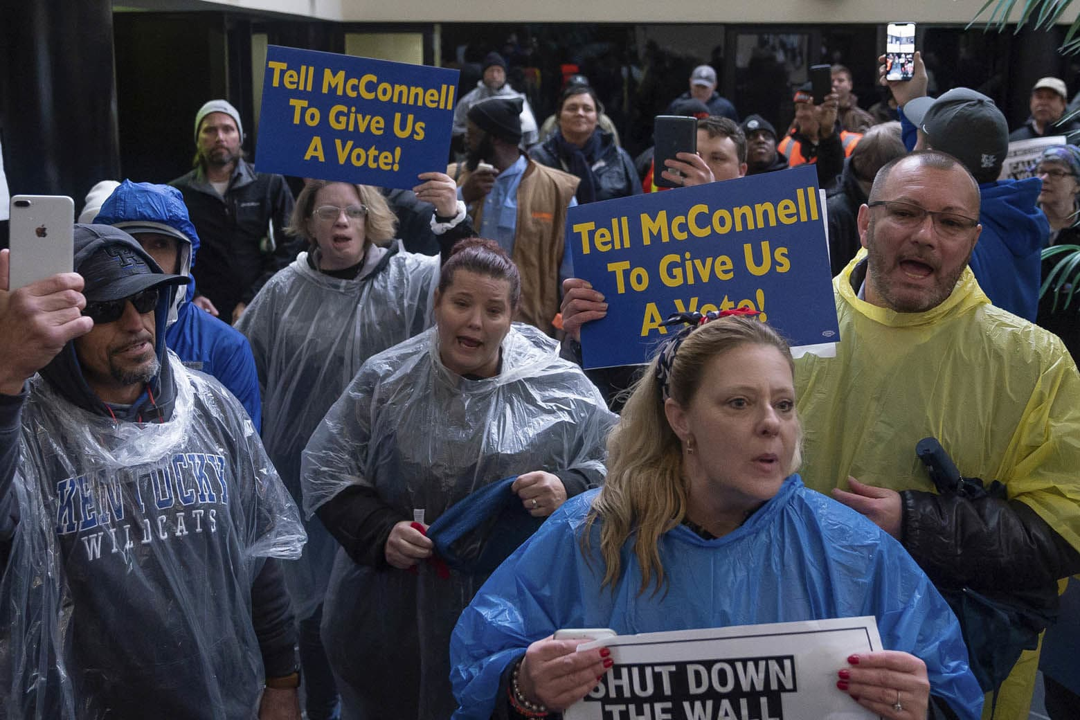 Furloughed government workers protest the government shutdown at the door of U.S. Sen. Mitch McConnell's office in Lexington, Ky., Wednesday, Jan 23, 2019. (AP Photo/Bryan Woolston)