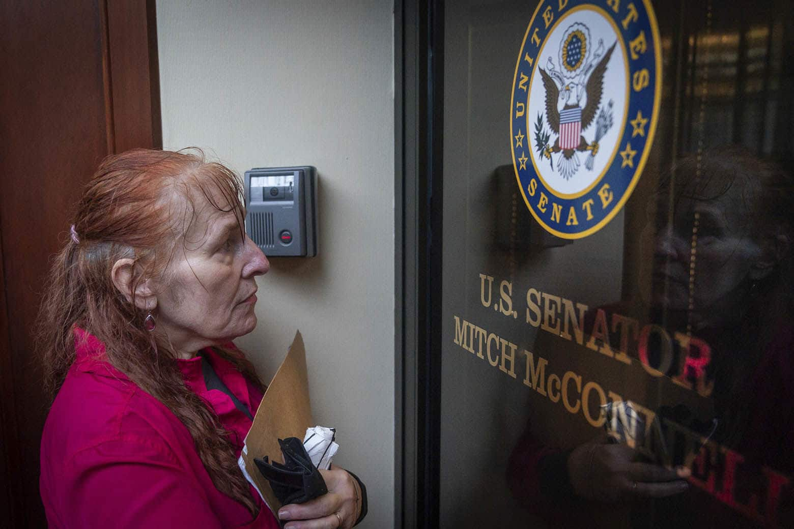 Reese Greer, a furloughed census worker, stands at the locked door of U.S. Sen. Mitch McConnell's office in Lexington, Ky., Wednesday, Jan 23, 2019, during a government shutdown protest. (AP Photo/Bryan Woolston)