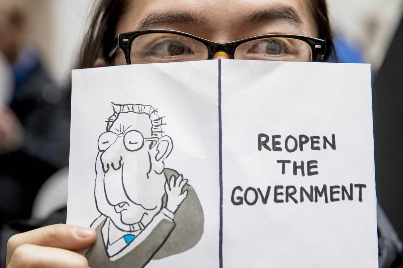 """A furloughed government worker affected by the shutdown holds a sign that reads """"Reopen the Government"""" during a silent protest against the ongoing partial government shutdown on Capitol Hill in Washington, Wednesday, Jan. 23, 2019. (AP Photo/Andrew Harnik)"""