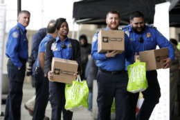Transportation Security Administration employees carry boxes of non perishables and bags of produce received from the Community Food Bank at a drive at Newark Liberty International Airport to help government employees who are working without pay during the partial government shutdown, Wednesday, Jan. 23, 2019, in Newark, N.J. (AP Photo/Julio Cortez)