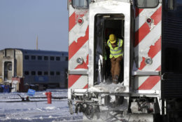 A worker clears snow from a train at the Metra Western Avenue Yard, Tuesday, Jan. 29, 2019, in Chicago. The extreme cold and record-breaking temperatures are crawling into a swath of states spanning from North Dakota to Missouri and into Ohio after a powerful snowstorm pounded the region earlier this week. (AP Photo/Kiichiro Sato)