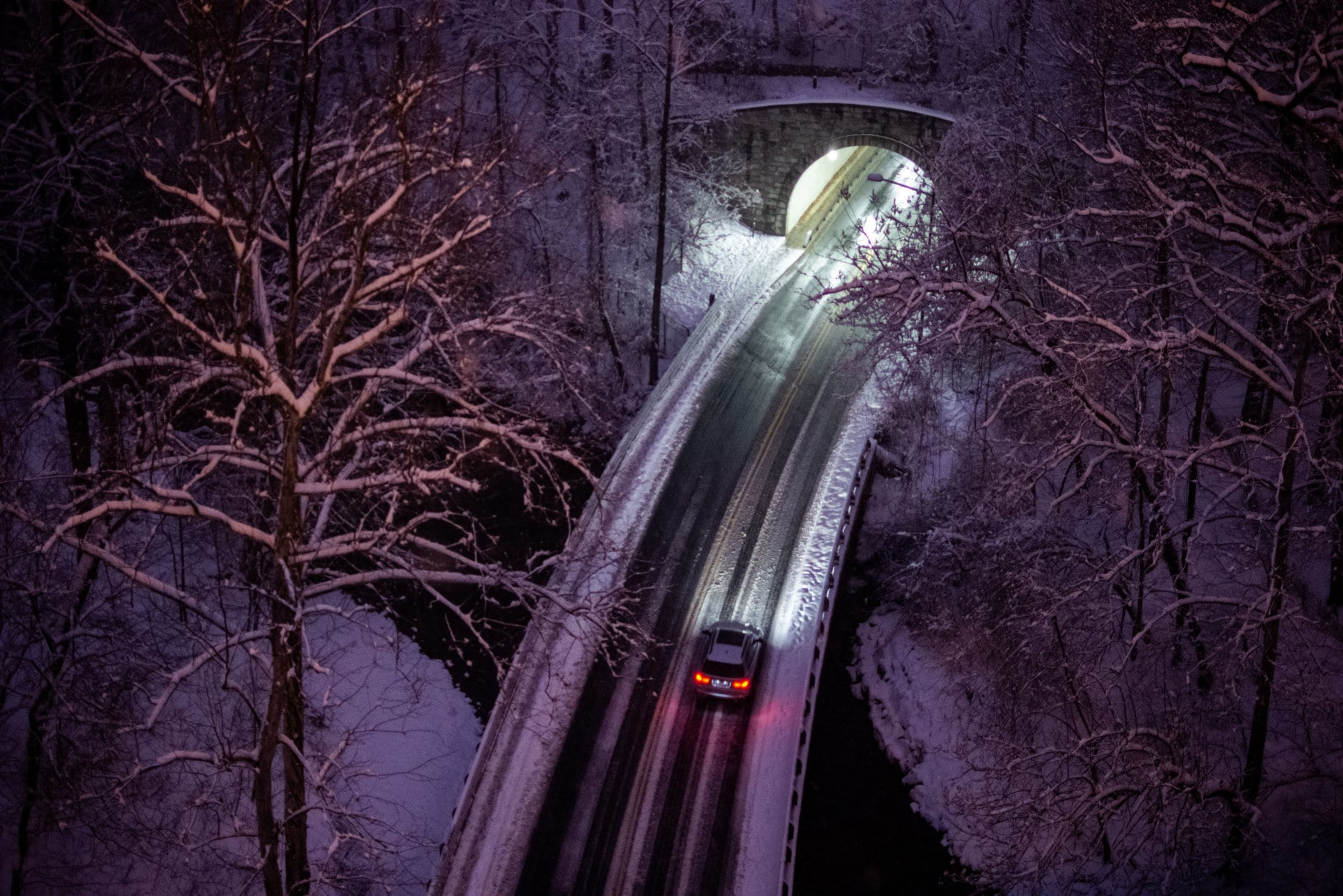 A lone car heads into north on Beach Drive, seen from the Duke Ellington Memorial Bridge between Woodley Park and Adams Morgan on Sunday evening. Roads were passable but still slick, amid a wonderland of blanketed trees in Rock Creek Park. (WTOP/Alejandro Alvarez)