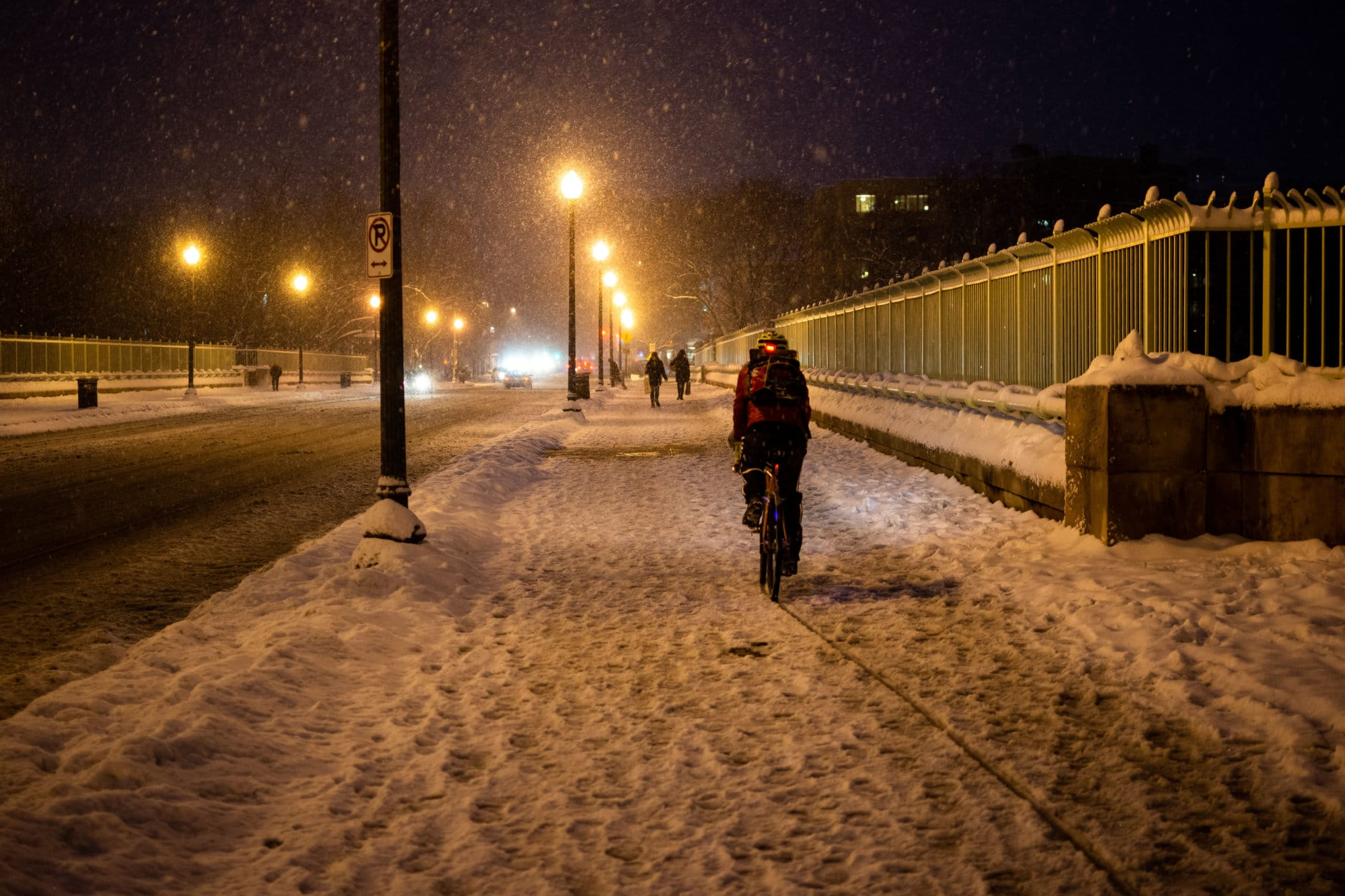A cyclist carves a line through the slush on the Duke Ellington Memorial Bridge, looking west toward Woodley Park on Sunday evening. Much of the sidewalk heading into Adams Morgan remained untreated, save for a small number of residents shoveling snow. (WTOP/Alejandro Alvarez)