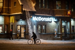 Snow drifts down from the roof of a McDonald's restaurant in Adams Morgan. Despite the slush, life in one of the D.C.'s most popular neighborhoods went on largely as normal on Sunday night, with most bars and stores still open. (WTOP/Alejandro Alvarez)