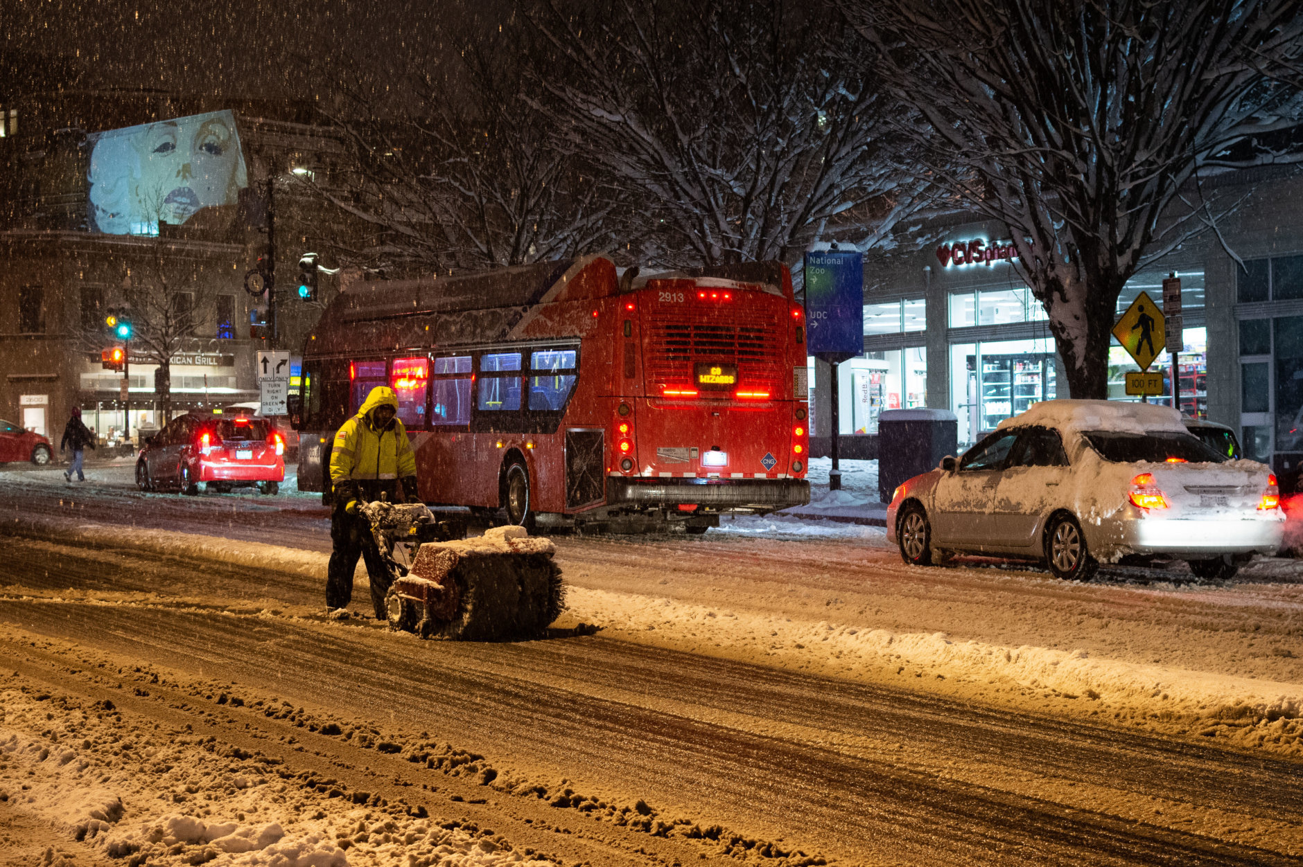 Work was underway to clear Calvert Street, NW on Sunday night, which had again become a slushy mess with heavier bands of snow moving into the area after a lull during the day. Temperatures were expected to drop further overnight, with a clear chance of widespread icing of roadways into Monday morning.(WTOP/Alejandro Alvarez)