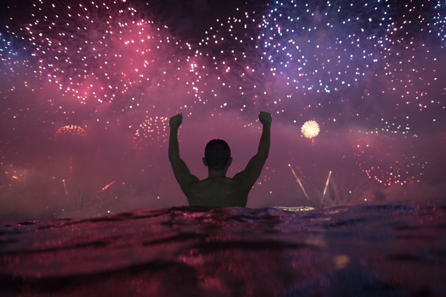 A man watches the fireworks exploding over Copacabana Beach during the New Year's celebrations in Rio de Janeiro, Brazil, Tuesday, Jan. 1, 2019. (AP Photo/Leo Correa)