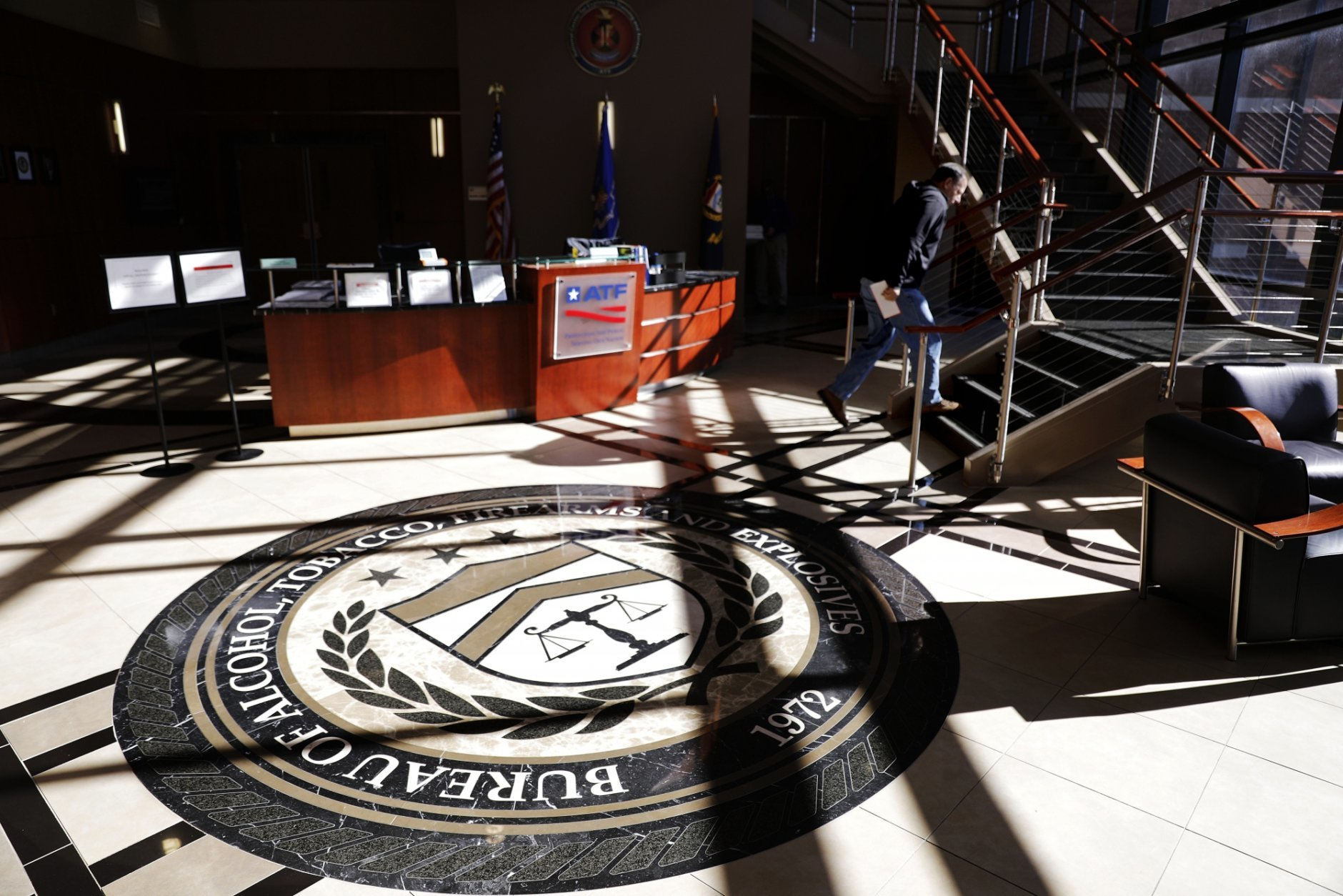 A worker walks through the empty lobby of the federal Bureau of Alcohol, Tobacco, Firearms and Explosives' National Center for Explosives Training and Research in Huntsville, Ala., Wednesday, Jan. 9, 2019. About 70 federal agencies are located at the Army's sprawling Redstone Arsenal, and more than half the area economy is tied to Washington spending. (AP Photo/David Goldman)