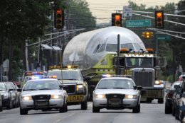 """US Airways jet, flight 1549, is trucked onto local streets after leaving J. Supor and Sons warehouse in Harrison, N.J. Saturday, June 4, 2011. The plane that splash-landed in the Hudson River in 2009, making a national hero of pilot Chesley """"Sully"""" Sullenberger, is being moved to an aviation museum in North Carolina, where it will be put on permanent display. (AP Photo/Bill Kostroun)"""