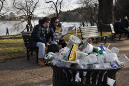 A trash can overflows as people site outside of the Martin Luther King Jr. Memorial by the Tidal Basin, Thursday, Dec. 27, 2018, in Washington, during a partial government shutdown. Chances look slim for ending the partial government shutdown any time soon. Lawmakers are away from Washington for the holidays and have been told they will get 24 hours' notice before having to return for a vote. Washington area national parks will remain open during the partial government shutdown, but without visitor center services. (AP Photo/Jacquelyn Martin)