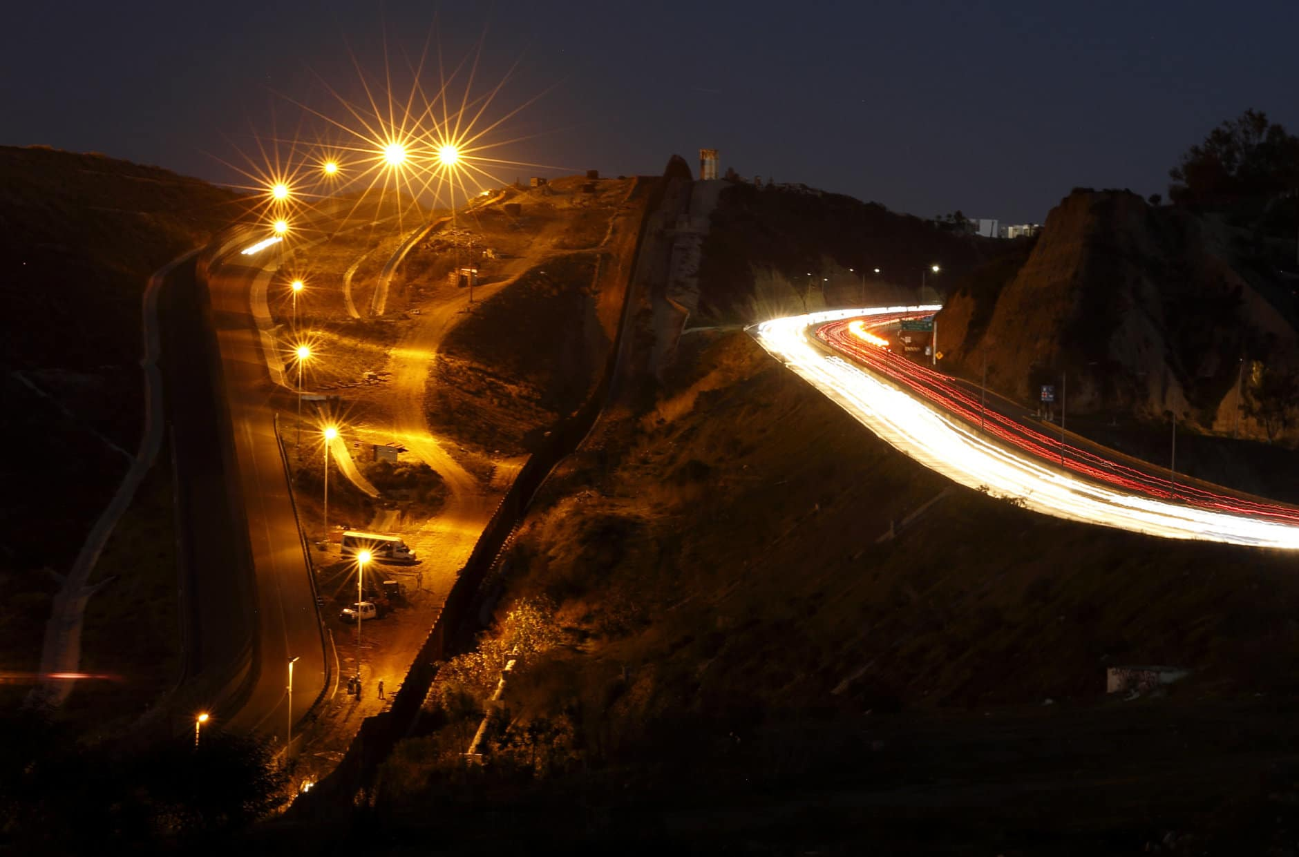 "Floodlights from the U.S,, left, illuminate multiple border walls, center, as traffic flows along a street Monday, Jan. 7, 2019, in Tijuana, Mexico. With no breakthrough in sight, President Donald Trump will argue his case to the nation Tuesday night that a ""crisis"" at the U.S.-Mexico border requires the long and invulnerable wall he's demanding before ending the partial government shutdown. (AP Photo/Gregory Bull)"