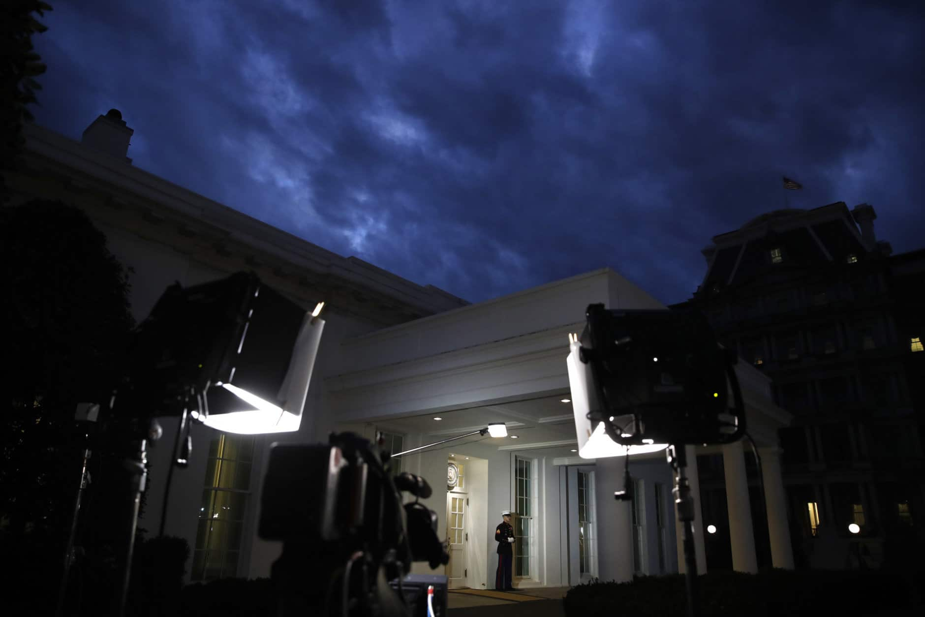 A Marine stands by the door to the West Wing of the White House, Tuesday Jan. 8, 2019, in Washington, as television lights are at the ready a few hours before President Donald Trump is expected to make an address to the nation. (AP Photo/Jacquelyn Martin)