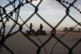 "Two U.S. Border Patrol agents talk along the beach in San Diego, Wednesday, Jan. 9, 2019, seen through razor wire lining the border wall from Tijuana, Mexico. U.S. President Donald Trump walked out of his negotiating meeting with congressional leaders Wednesday — ""I said bye-bye,"" he tweeted— as efforts to end the 19-day partial government shutdown fell into deeper disarray over his demand for billions of dollars to build a wall on the U.S.-Mexico border. (AP Photo/Gregory Bull)"