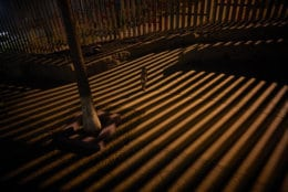 A boy plays as floodlights from the United States filter through the border wall Friday, Jan. 11, 2019, in Tijuana, Mexico. The partial U.S. government shutdown was on track Friday to become the longest closure in U.S. history as President Donald Trump and nervous Republicans look for a way out of the mess. A solution couldn't come soon enough for federal workers who got pay statements Friday but no pay. (AP Photo/Gregory Bull)