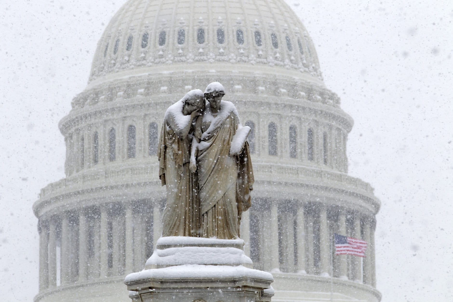 The U.S. Capitol is see behind the Peace Monument during a snowstorm, as a partial government shutdown stretches into its third week at Capitol Hill in Washington Sunday, Jan. 13, 2019. With the standoff over paying for his long-promised border wall dragging on, the president's Oval Office address and visit to the Texas border over the past week failed to break the logjam and left aides and allies fearful that the president has misjudged Democratic resolve and is running out of negotiating options. (AP Photo/Jose Luis Magana)