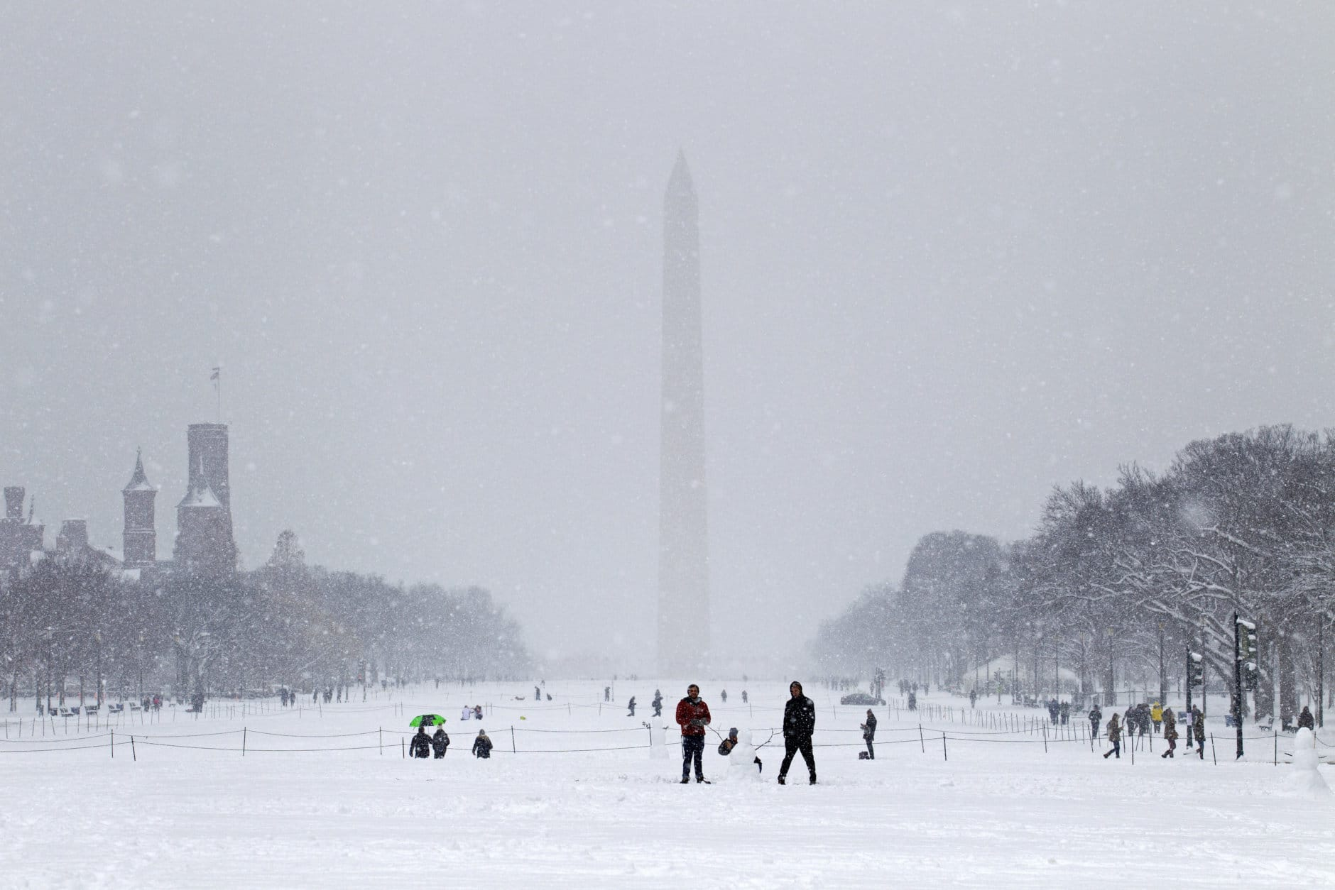 People play with snow at the National Mall during a snowstorm, as a partial government shutdown stretches into its third week at Capitol Hill in Washington Sunday, Jan. 13, 2019. With the standoff over paying for his long-promised border wall dragging on, the president's Oval Office address and visit to the Texas border over the past week failed to break the logjam and left aides and allies fearful that the president has misjudged Democratic resolve and is running out of negotiating options. (AP Photo/Jose Luis Magana)