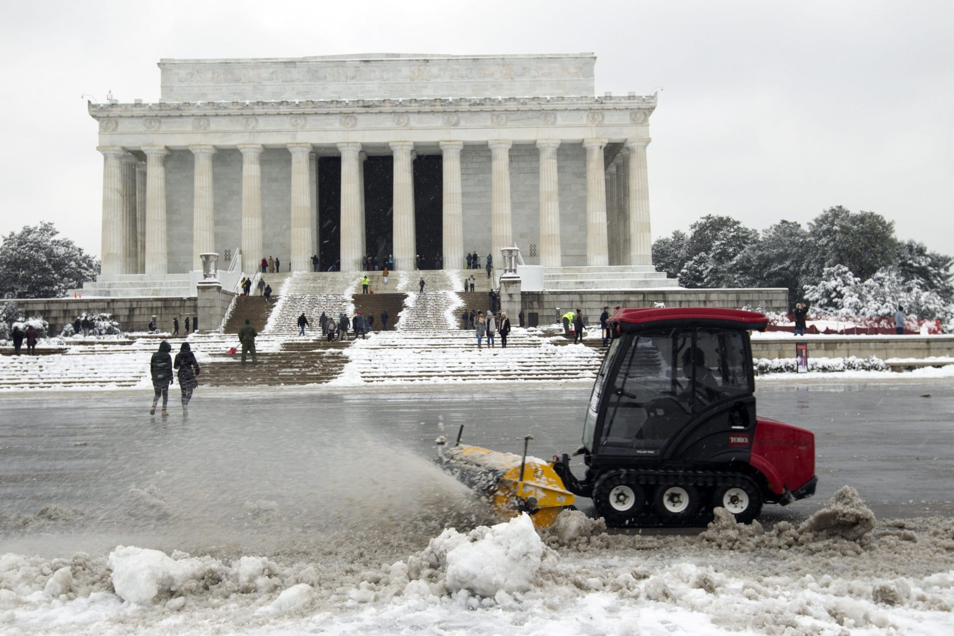 Park service workers clean the snow outside of Lincoln Memorial, during a snowstorm, as a partial government shutdown stretches into its third week at Capitol Hill in Washington Sunday, Jan. 13, 2019. With the standoff over paying for his long-promised border wall dragging on, the president's Oval Office address and visit to the Texas border over the past week failed to break the logjam and left aides and allies fearful that the president has misjudged Democratic resolve and is running out of negotiating options. (AP Photo/Jose Luis Magana)