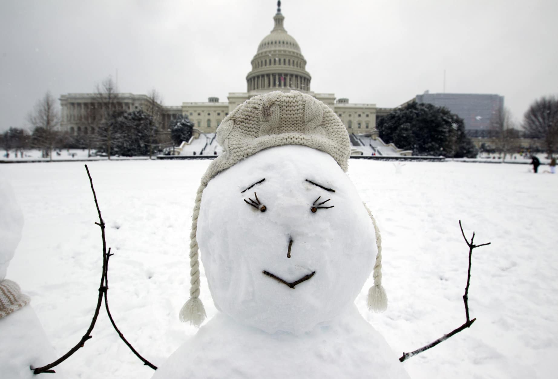 The U.S. Capitol is seen behind a snowman during a snowstorm, as a partial government shutdown stretches into its third week at Capitol Hill in Washington Sunday, Jan. 13, 2019. With the standoff over paying for his long-promised border wall dragging on, the president's Oval Office address and visit to the Texas border over the past week failed to break the logjam and left aides and allies fearful that the president has misjudged Democratic resolve and is running out of negotiating options. (AP Photo/Jose Luis Magana)