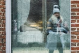 A tourist is reflected in a window of the closed building housing the Liberty Bell, in Philadelphia, Wednesday, Jan. 16, 2019. The building is closed due to the partial government shutdown. (AP Photo/Matt Rourke)