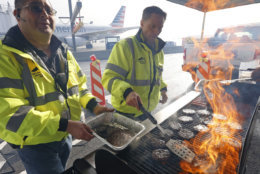 Airport operation workers wearing fluorescent safety jackets flipped burgers and hot dogs on a grill set up on a tarmac in front of a plane at Salt Lake City International Airport, Wednesday, Jan. 16, 2019, in Salt Lake City. In Salt Lake City, airport officials treated workers from the TSA, FAA and Customs and Border Protection to a free barbecue lunch as a gesture to keep their spirits up during a difficult time. (AP Photo/Rick Bowmer)