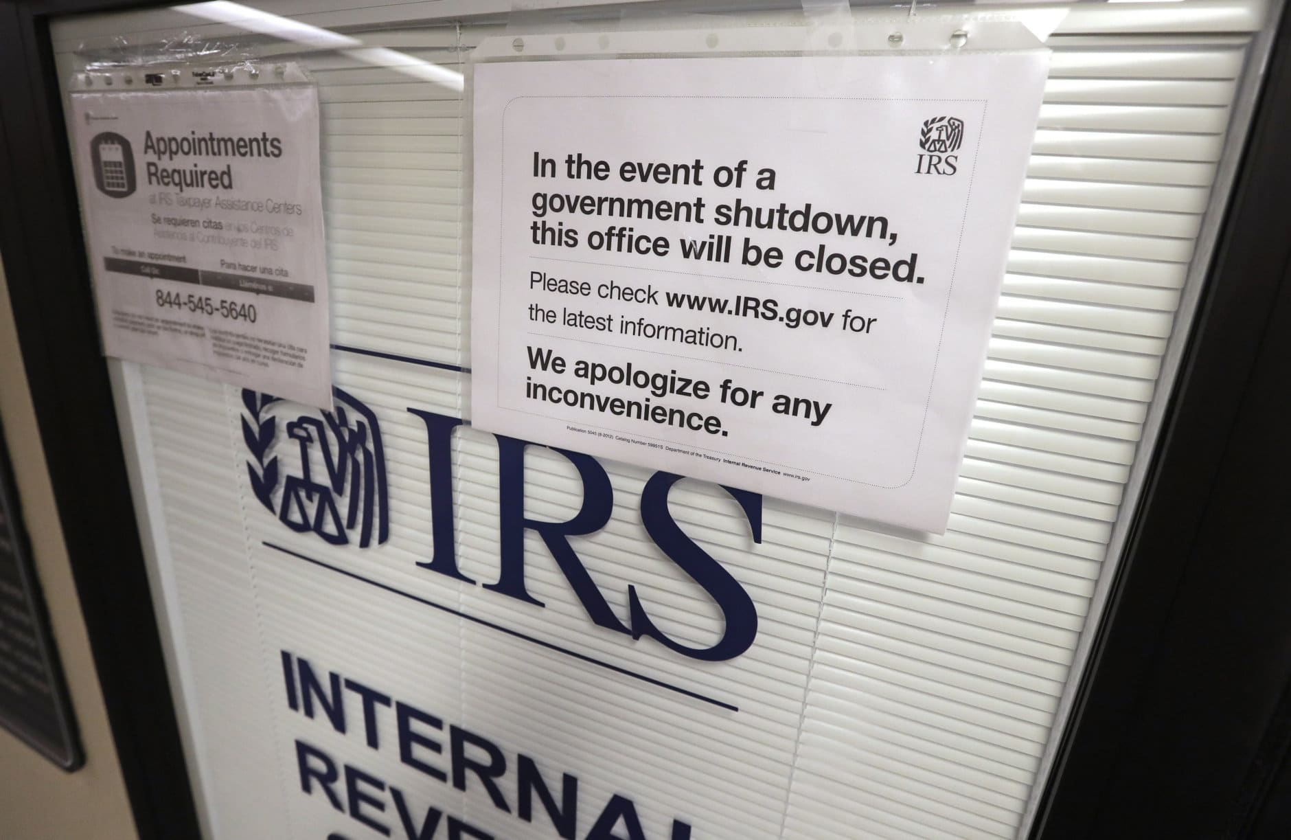 Doors at the Internal Revenue Service (IRS) in the Henry M. Jackson Federal Building are locked and covered with blinds as a sign posted advises that the office will be closed during the partial government shutdown Wednesday, Jan. 16, 2019, in Seattle. The shutdown is in its fourth week with no end in sight. (AP Photo/Elaine Thompson)