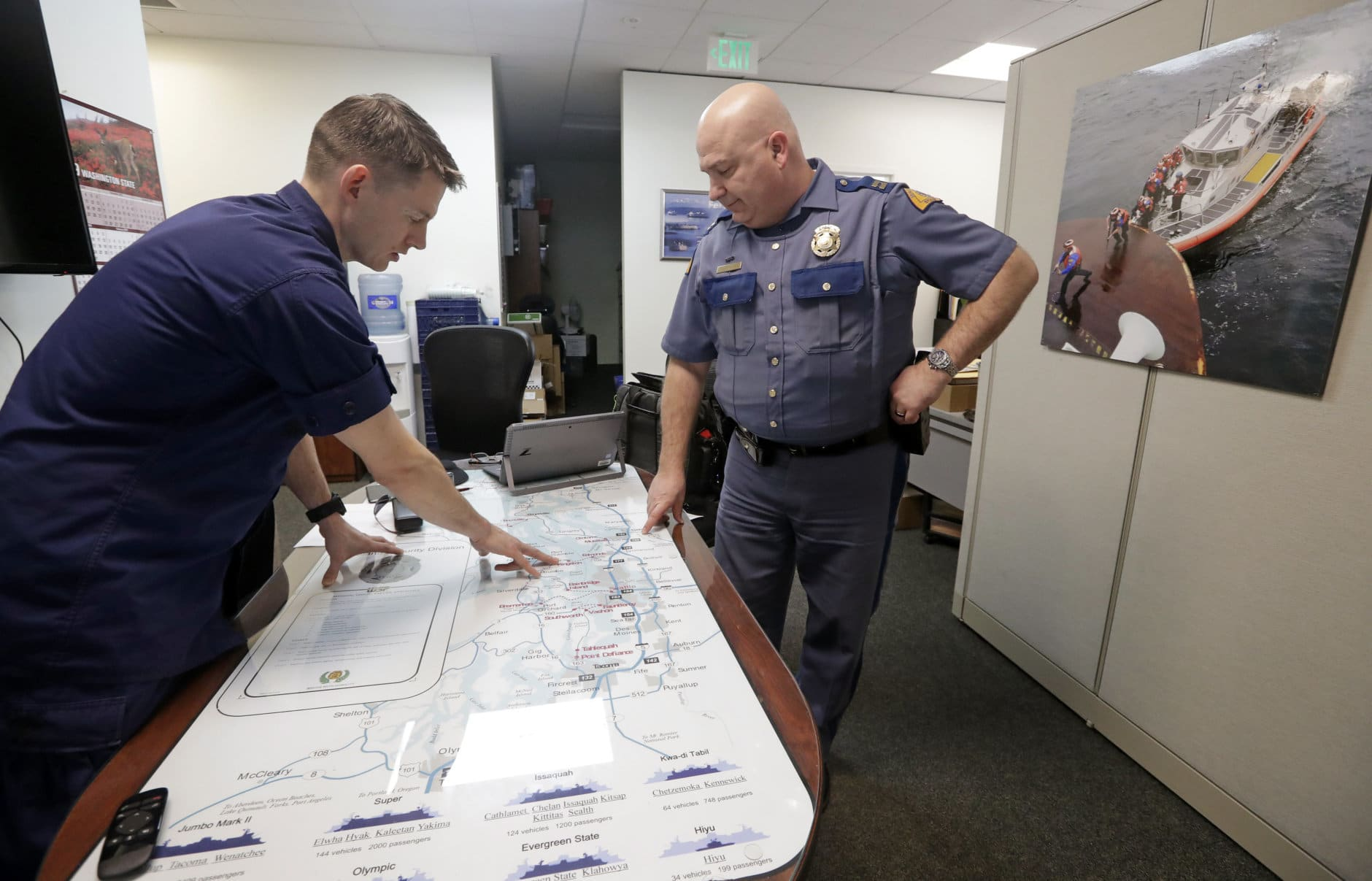 U.S. Coast Guard Lt. Cmdr. Blair Sweigert, left, who missed a paycheck a day earlier during the partial government shutdown, works with Washington State Patrol Capt. Dan Atchison in a shared office where they coordinate marine security at Sector Puget Sound base Wednesday, Jan. 16, 2019, in Seattle. The Coast Guard is part of the U.S. Department of Homeland Security, which is unfunded during the shutdown, now in its fourth week. (AP Photo/Elaine Thompson)