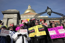 Internal Revenue Service employees Brian Lanouette, of Merrimack, N.H., center right, and Mary Maldonado, of Dracut, Mass., right, join with others as they display placards during a rally by federal employees and supporters, Thursday, Jan. 17, 2019, in front of the Statehouse, in Boston, held to call for an end of the partial shutdown of the federal government. (AP Photo/Steven Senne)