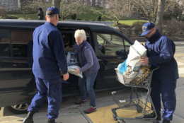 In this Thursday, Jan. 17, 2019 photo, Christine Lamb, president and founder of the nonprofit group Animal House Inc., in nearby Waterford, Conn., delivers bags of donated pet food to Coast Guardsmen helping at a pop-up food pantry created on the grounds of the U.S. Coast Guard Academy in New London, Conn. Hundreds of Coast Guard civilian and non-civilian employees working at the academy and at other Coast Guard installations have been impacted by the partial federal shutdown and have not received a paycheck in weeks. (AP Photo/Susan Haigh)