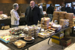 """In this Thursday, Jan. 17, 2019 photo, retired U.S. Coast Guard Adm. Thad Allen, center, speaks with Felicitas Rendon, wife of Rear Adm. James E. Rendon, superintendent of the Coast Guard Academy in New London, Conn. Allen was visiting a pop-up food pantry created at a school to help hundreds of civilian and non-civilian Coast Guard employees affected by the partial federal government shutdown. Allen called the shutdown a """"wound"""" that's been inflicted """"by our own government."""" (AP Photo/Susan Haigh)"""