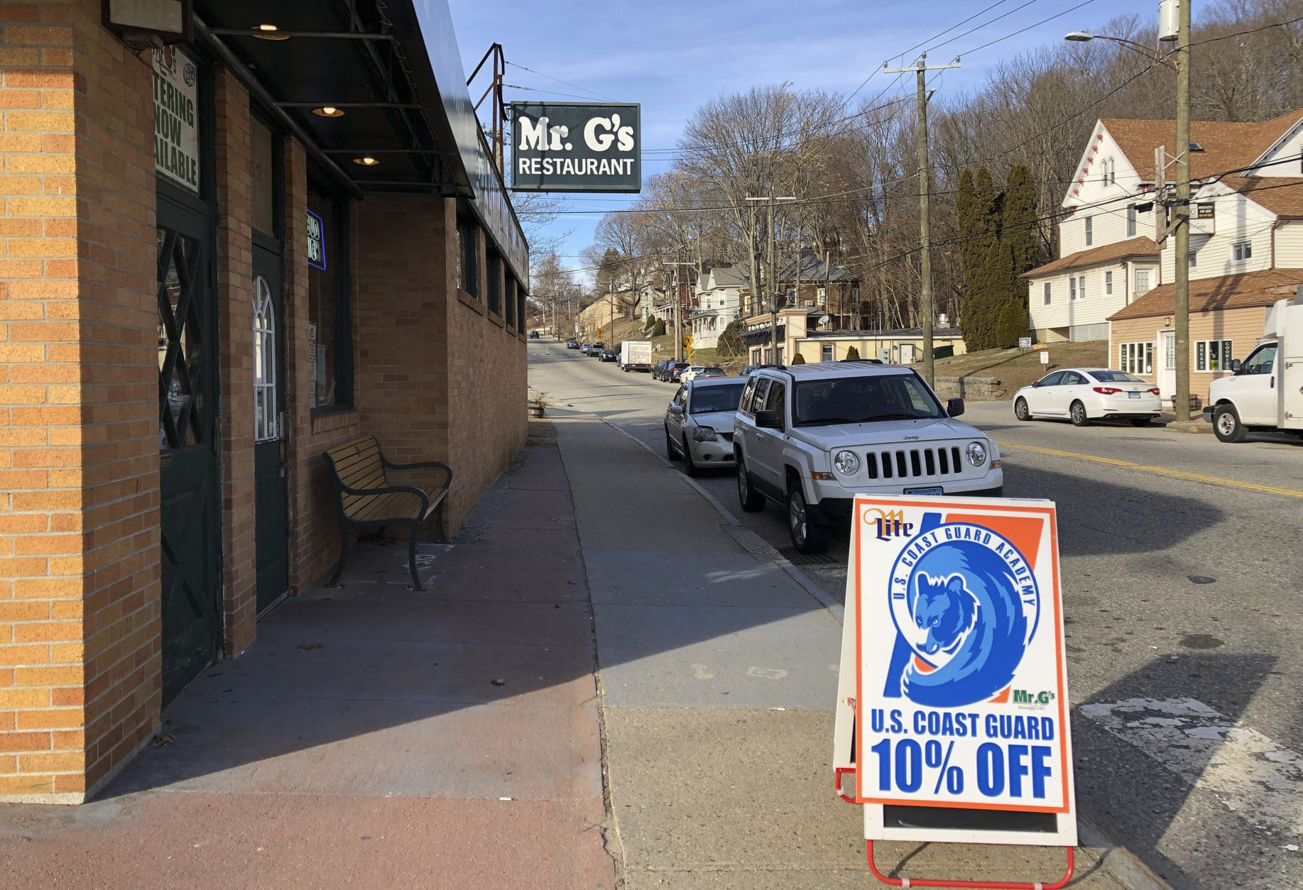In this Thursday, Jan. 17, 2019 photo, a sign advertises a discount offered by Mr. G's in New London, Conn., to the hundreds of civilian and non-civilian Coast Guard Employees who work in the area. Located a short distance from the U.S. Coast Guard Academy, the restaurant and bar is a popular spot for academy cadets, staff and others. Manager Peter Farnan says he's beginning to see signs of the shutdown, estimating his business has dropped about 10 percent. (AP Photo/Susan Haigh)