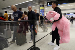 Carlos Gonzalez, right, watches as his daughter and other family members wait in line at a security checkpoint at Miami International Airport, Friday, Jan. 18, 2019, in Miami. The three-day holiday weekend is likely to bring bigger airport crowds. (AP Photo/Lynne Sladky)