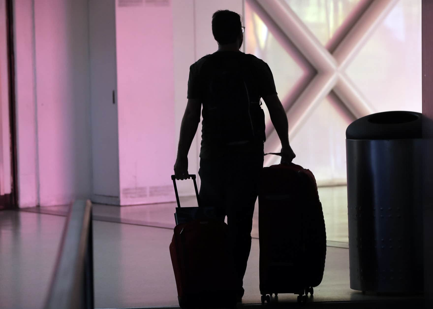 A traveler walks through Miami International Airport, Friday, Jan. 18, 2019, in Miami. The three-day holiday weekend is likely to bring bigger airport crowds. (AP Photo/Lynne Sladky)