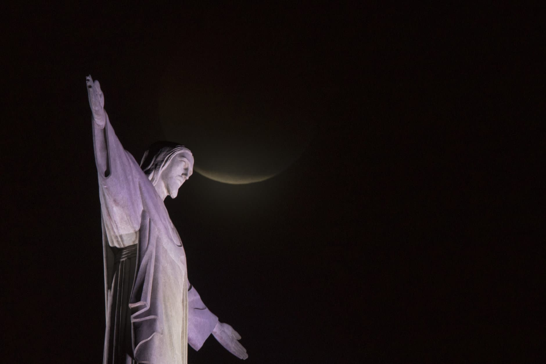 A blood moon rises above Christ the Redeemer statue during a lunar eclipse in Rio de Janeiro, Brazil, Monday, Jan. 21, 2019. It's also the year's first supermoon, when a full moon appears a little bigger and brighter thanks to its slightly closer position to Earth. (AP Photo/Leo Correa)