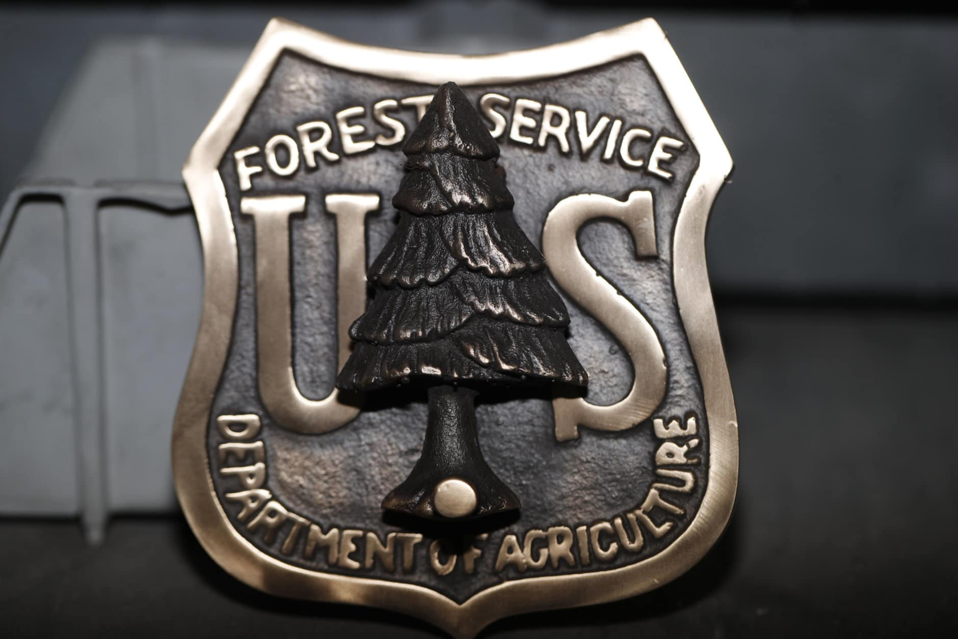 A door knocker made for the U.S. Forest Service is shown at Western Heritage Co. Thursday, Jan. 24, 2019, in Loveland, Colo. Lynch saw online orders collapse almost immediately after the government shut down Dec. 22. The company sells buckles, keychains, commemorative coins and badges to employees of the Fish and Wildlife Service, the Forest Service, the Bureau of Land Management and other agencies. It also sells patches and some clothing. (AP Photo/David Zalubowski)