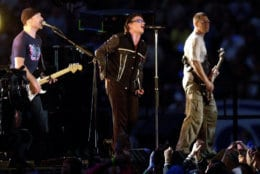 """FILE - In this Feb. 3, 2002 file photo, The Edge, from left, Bono and Adam Clayton, of U2, perform during the halftime show of Super Bowl XXXVI at the Louisiana Superdome in New Orleans. At the first Super Bowl following the 2001 terrorist attacks, U2 performed """"Where the Streets Have No Name"""" as a giant scrim behind them unfurled names of the Sept. 11 victims. (AP Photo/Tony Gutierrez, File)"""
