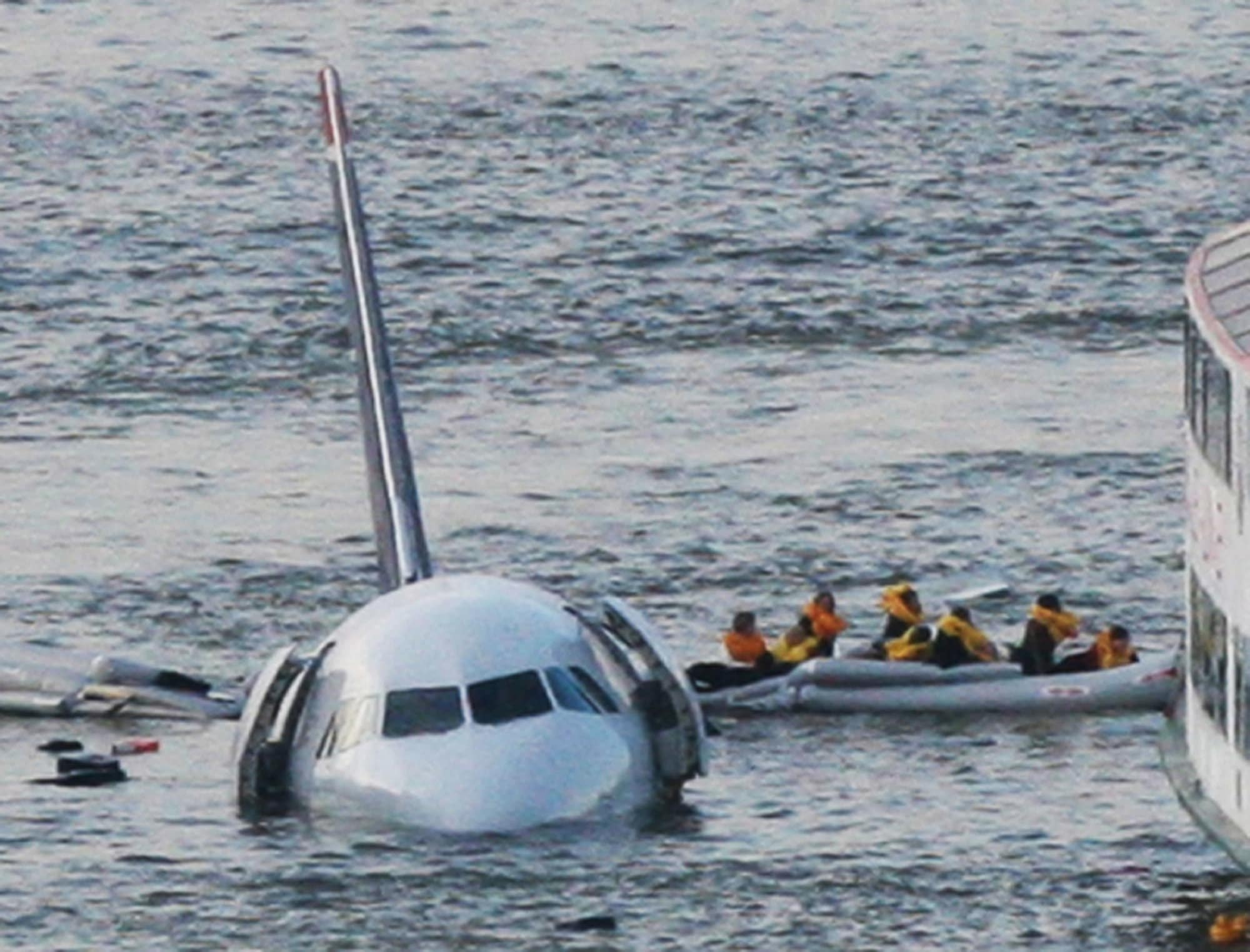 FILE - In this Jan. 15, 2009 file photo, passengers in an inflatable raft move away from US Airways Flight 1549 that went down in the Hudson River in New York. The jet ditched in the Hudson River after both engines failed when they ingested birds shortly after takeoff. All 155 people on board were safe; Captain Chesley Sullenberger and other crew members were hailed as heroes. (AP Photo/Bebeto Matthews, File)