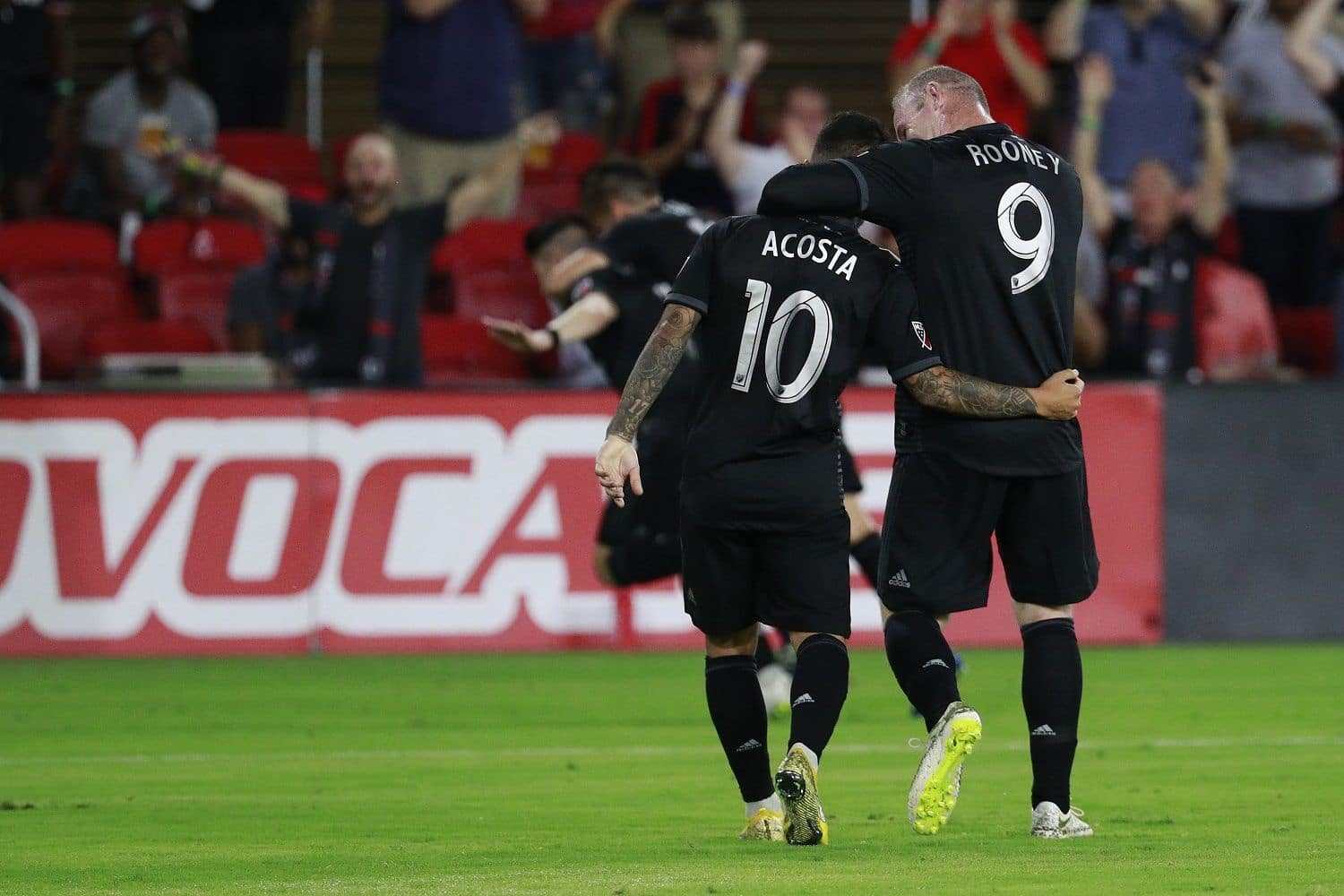 WASHINGTON, DC - JULY 14: Wayne Rooney #9 and Luciano Acosta #10 of D.C. United celebrate after Paul Arriola #7 (not pictured) scored a goal in the second half against the Vancouver Whitecaps at Audi Field on July 14, 2018 in Washington, DC. (Photo by Patrick McDermott/Getty Images)