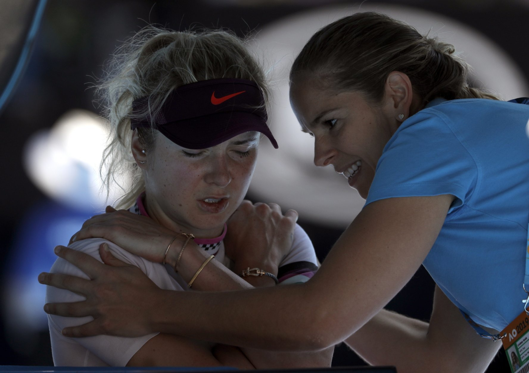 Ukraine's Elina Svitolina receives treatment from a trainer during her quarterfinal against Japan's Naomi Osaka at the Australian Open tennis championships in Melbourne, Australia, Wednesday, Jan. 23, 2019. (AP Photo/Mark Schiefelbein)
