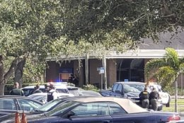 Law enforcement officials take cover outside a SunTrust Bank branch, Wednesday, Jan. 23, 2019, in Sebring, Fla. Authorities say they've arrested a man who fired shots inside the Florida bank. (The News Sun via AP)