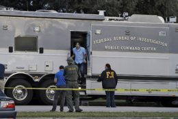 Law enforcement officials climb out a FBI mobile command center vehicle that is parked in front of a SunTrust Bank branch, Wednesday, Jan. 23, 2019, in Sebring, Fla., where authorities say five people were shot and killed. (AP Photo/Chris O'Meara)