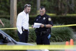Law enforcement officers look over papers out in front of a SunTrust bank, Wednesday, Jan. 23, 2019, in Sebring, Fla., where authorities say five people were shot and killed (AP Photo/Chris O'Meara)
