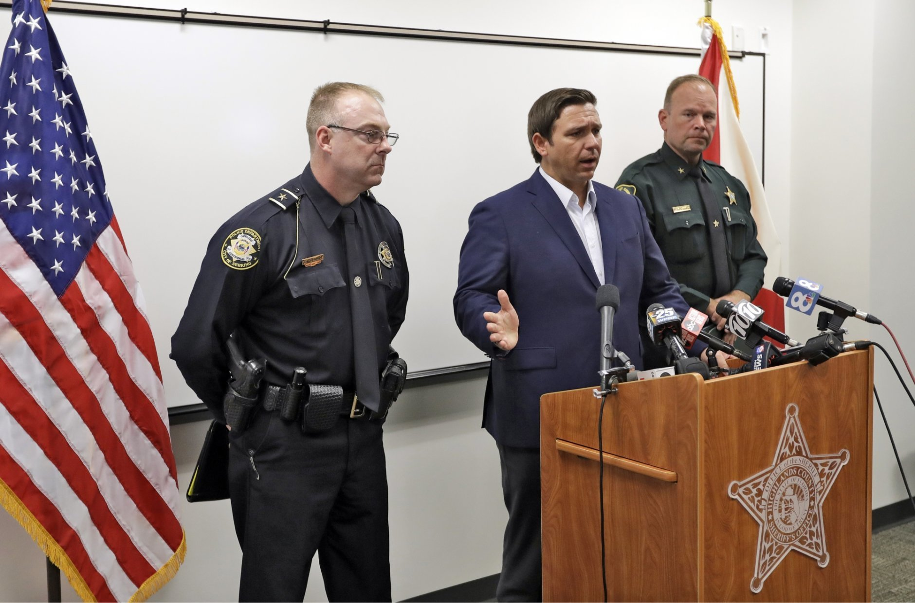 Florida Gov. Ron DeSantis, center, gestures as he speaks during a news conference alongside Sebring, Fla., police chief Karl Hoglund, left, and Highlands County sheriff Paul Blackman, right, Wednesday, Jan. 23, 2019, in Sebring, Fla., after authorities said five people were shot and killed at a SunTrust bank branch. (AP Photo/Chris O'Meara)