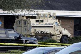 A Highlands County Sheriff's SWAT vehicle is stationed out in front of a SunTrust Bank branch, Wednesday, Jan. 23, 2019, in Sebring, Fla., where authorities say five people were shot and killed. (AP Photo/Chris O'Meara)