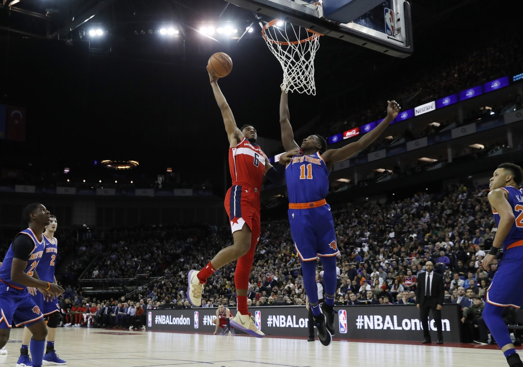 Washington Wizards forward Troy Brown Jr. (6), left, drives to the basket as New York Knicks guard Frank Ntilikina (11) defends, during an NBA basketball game between New York Knicks and Washington Wizards at the O2 Arena, in London, Thursday, Jan.17, 2019. (AP Photo/Alastair Grant)